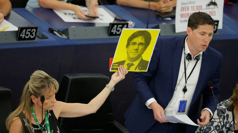 A Member of the European Parliament holds a portrait of former Catalan President Carles Puigdemont during the first plenary session of the newly elected European Parliament in Strasbourg
