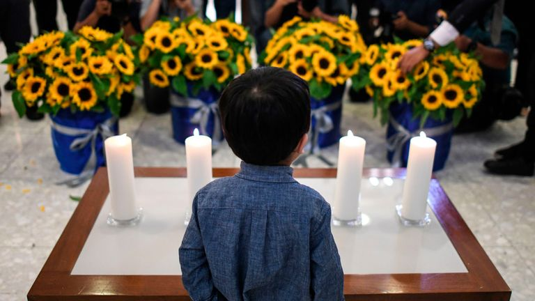 A boy stands in front of candles and flowers during a commemoration ceremony for passengers who perished aboard flight Malaysia Airlines flight MH17, which was shot down over eastern Ukraine five years ago at the Australian High Commission in Kuala Lumpur on July 17, 2019. (Photo by MOHD RASFAN / AFP) (Photo credit should read MOHD RASFAN/AFP/Getty Images)