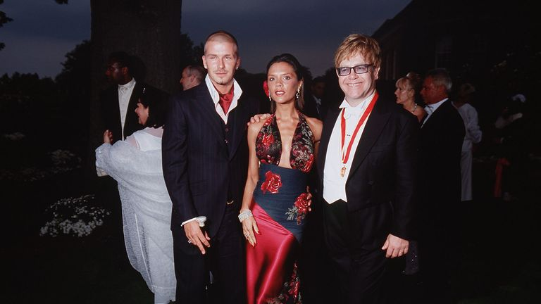 David Beckham (L) and his wife Victoria (C) pose for photos with singer Elton John (R) at the White Tie and Tiara Ball held at Elton John's Windsor mansion in London on July 5, 2001