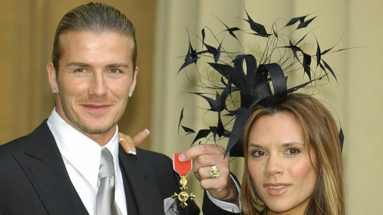 England's football captain David Beckham stands with his wife, Victoria, as he shows off the OBE (Officer of the Order of the British Empire) he received 27 November, 2003, from Britain's Queen Elizabeth II at London's Buckingham Palace