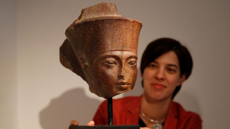 Laetitia Delaloye, head of antiquities of Christie's, poses for a photograph with an Egyptian brown quartzite head of Tutankhamen prior to its sale at Christie's auction house in London on Thursday