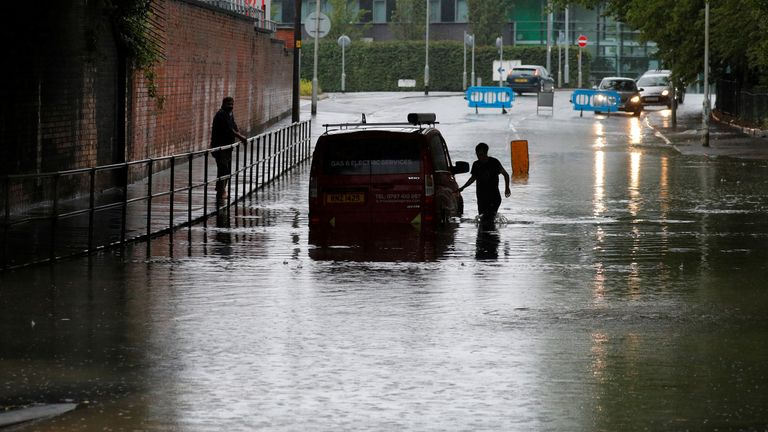 A van gets trapped by flooding in Manchester on Sunday