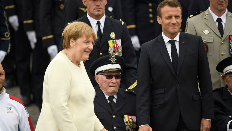 Emmanuel Macron and Angela Merkel stand with a World War Two veteran during the parade