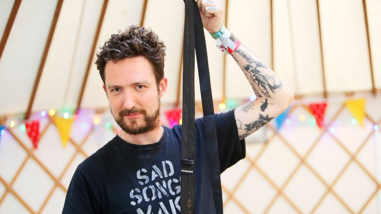 Frank Turner holding signed tie he donated to Oxfam. Pic: Oxfam