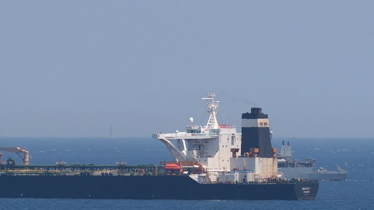 A British Royal Navy ship (back R) patrols near supertanker Grace 1 suspected of carrying crude oil to Syria in violation of EU sanctions after it was detained off the coast of Gibraltar