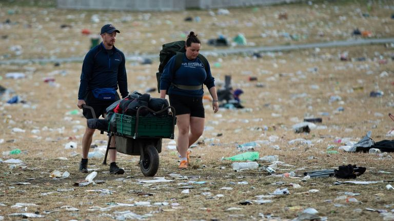 Festival goers leave the site ahead of a massive clean-up