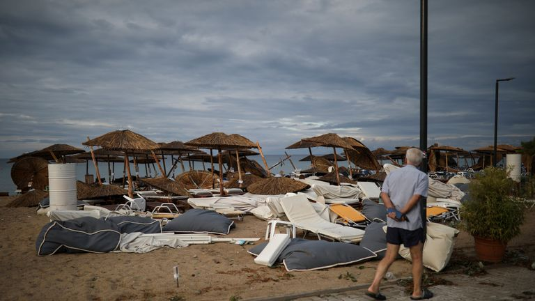 A man looks at damaged umbrellas and lounge chairs following heavy storms at the beach of the village of Nea Plagia, Greece, July 11, 2019. REUTERS/Alkis Konstantinidis