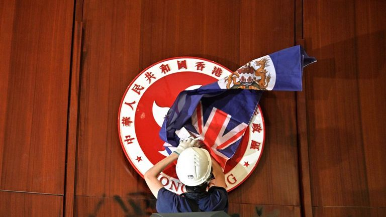 A protester covers the Hong Kong emblem with a British colonial flag at the Legislative Council building