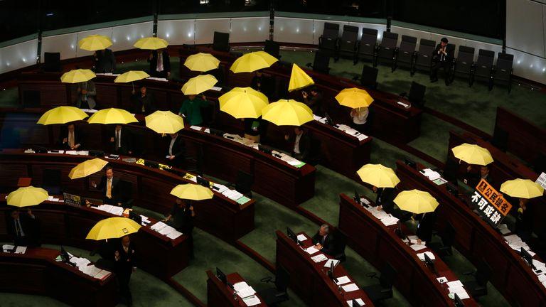 Pro-democracy Legislative Council members open yellow umbrellas during a meeting in 2015