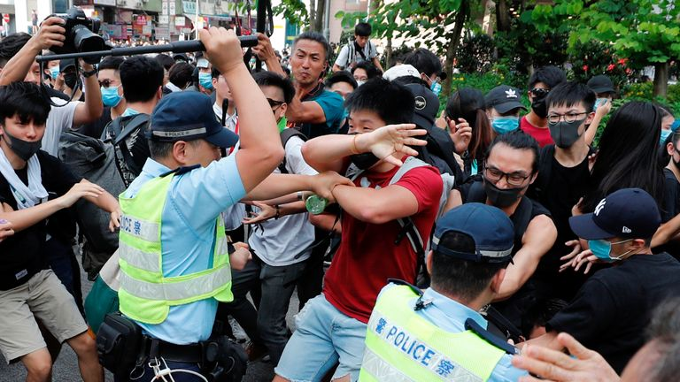 Police swing their batons at pro-democracy protesters at Sheung Shui