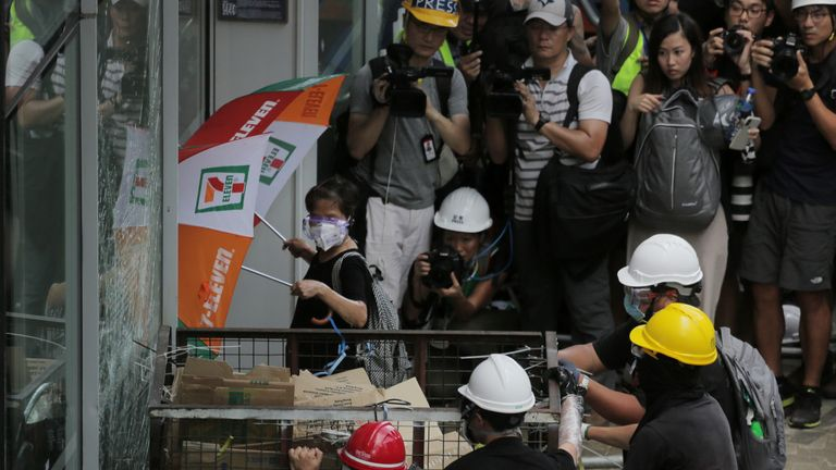Protesters try to push a metal cart through a closed entrance at the government headquarters