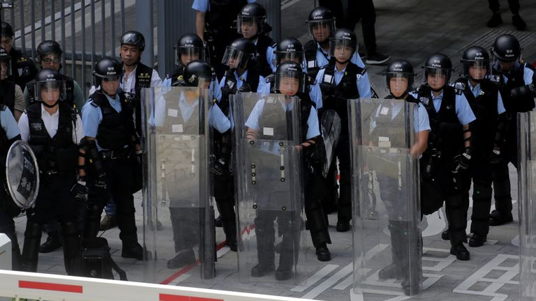 Police stand guard with shields