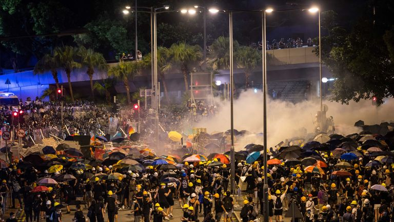 Police fire tear gas as they charge toward protesters outside the legislative council