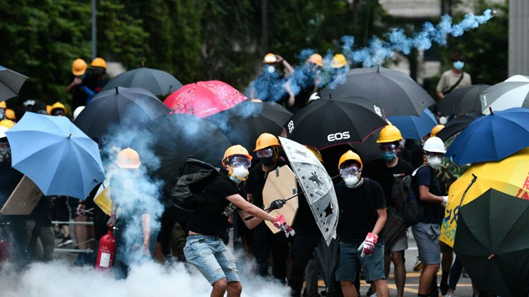 A protester throws tear gas back at police