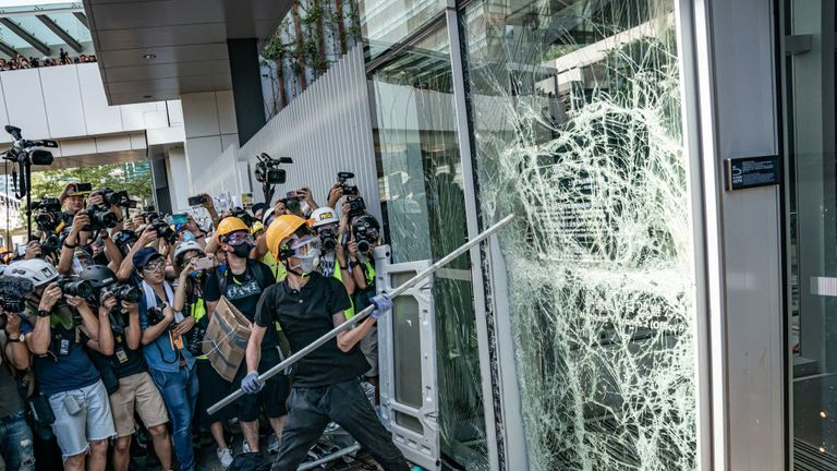 A protester uses a metal pole to break in to the Legislative Council building