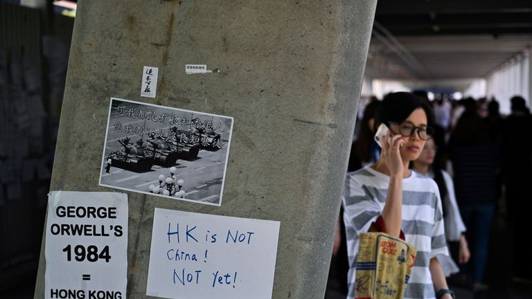 People walk past placards against the extradition law pasted on a wall near the Legislative Council