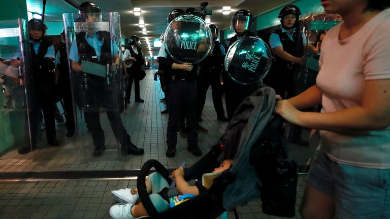 A woman pushes her pram past riot police in Hong Kong