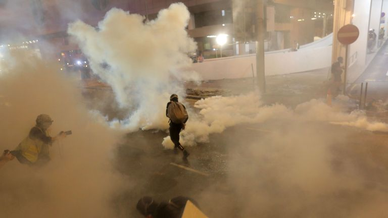 Protesters run from tear gas fired by police