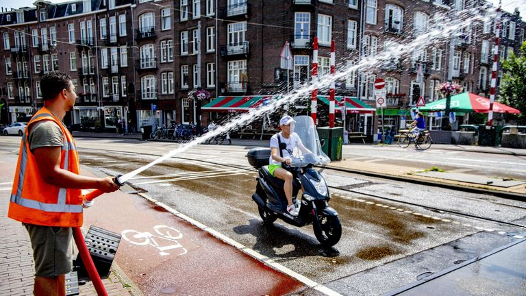 A municipal officer sprays water on the Wiegbrug bridge in Amsterdam in order to keep the road cool