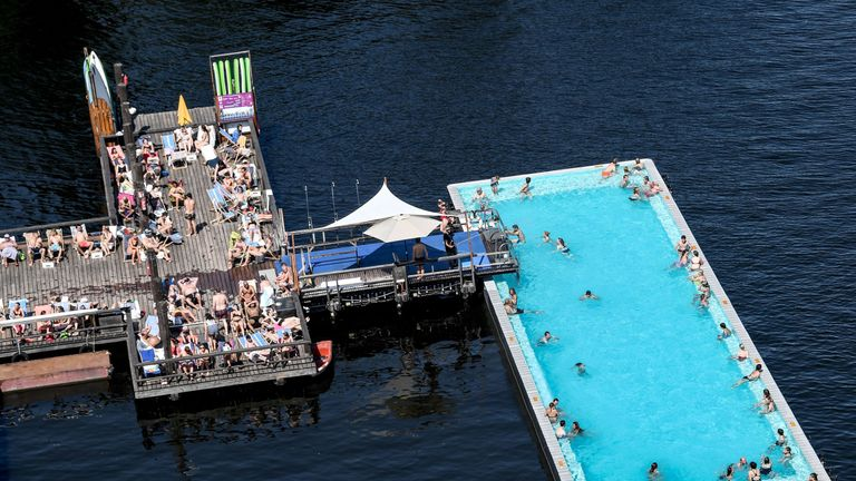 """People cool off in the public pool """"Badeschiff"""" (swimming pool ship) on river Spree in central Berlin"""