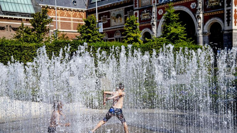 People play and refresh themselves in a fountain at the Museumplein square in Amsterdam