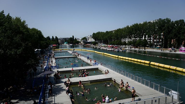 People cool off at floating pools set up on the Ourcq canal in Paris