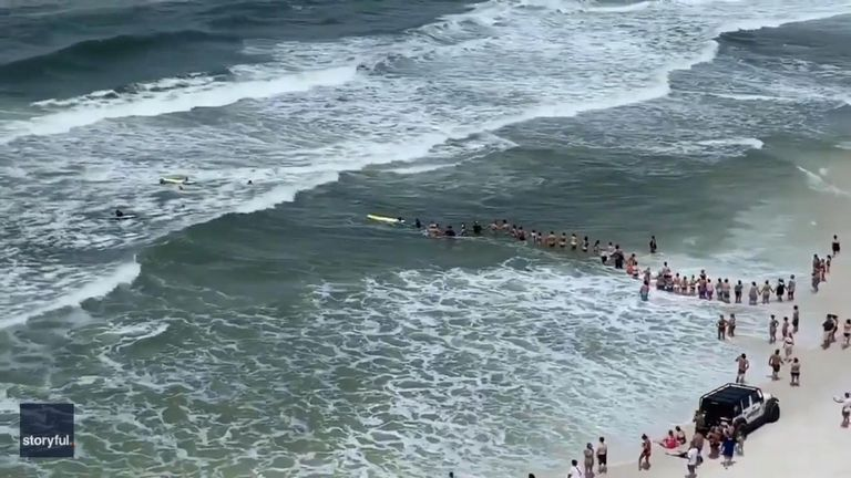 Beachgoers and rescue personnel formed a human chain, though at least one rescuer nonetheless had to swim out to the pair