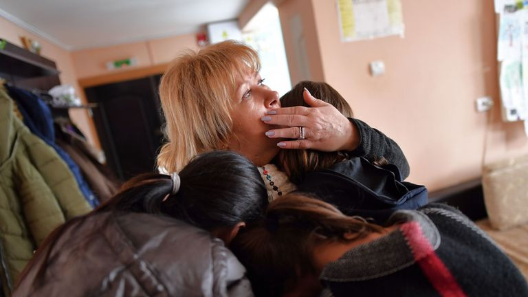 Iana Matei (C), a Romanian psychologist who takes care of minors who have been victims of human trafficking is embraced by some of the girls there at the reception center