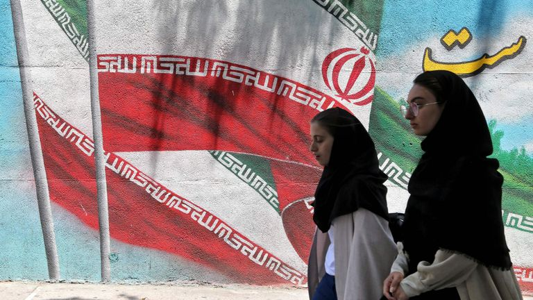 Iranian women walk past a mural painted with the Iranian flag in Tehran on June 25, 2019