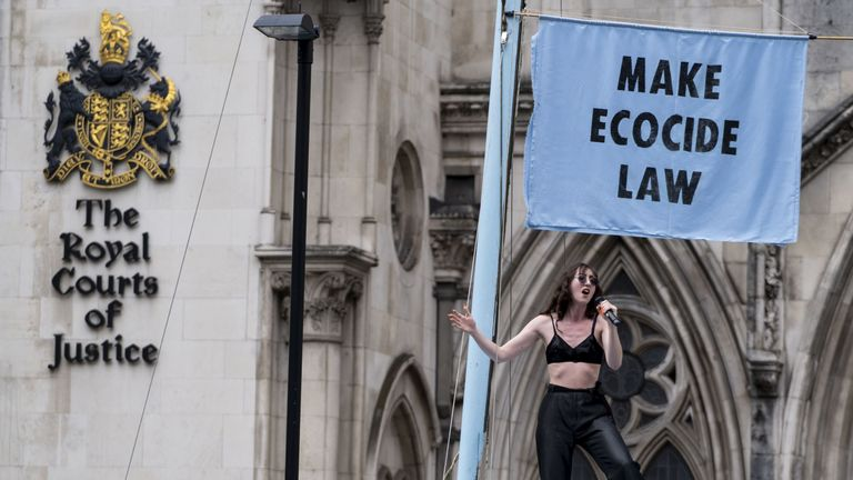 Singer Jessica Winter entertains demonstrators outside of The Royal Courts of Justice
