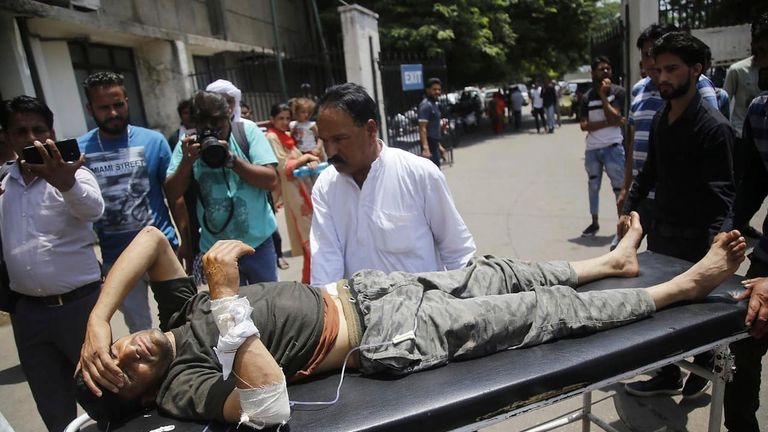 A passenger who got injured after an overcrowded minibus crashed into a gorge in Indian-controlled Kashmir is brought for treatment at a hospital in Jammu, India, Monday, July 1, 2019
