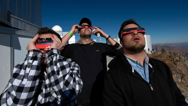 People watch a solar eclipse at La Silla European Southern Observatory (ESO) in La Higuera, Coquimbo Region, Chile, on July 02, 2019. - Tens of thousands of tourists braced Tuesday for a rare total solar eclipse that was expected to turn day into night along a large swath of Latin America's southern cone, including much of Chile and Argentina