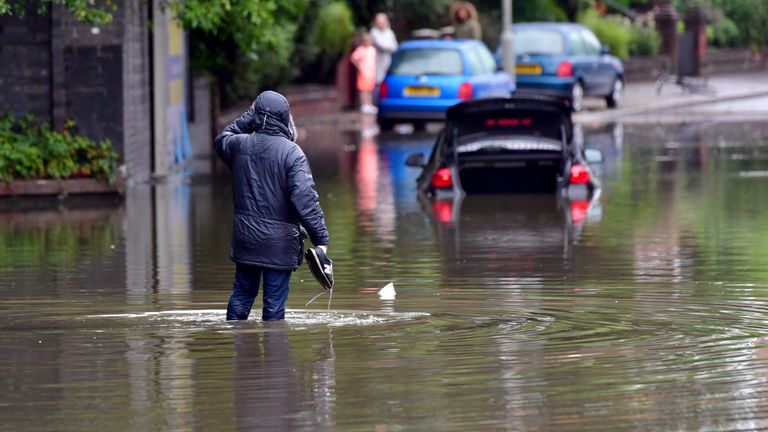 A man carries his trainers as he walks through floodwater near Levenshulme in Manchester on Sunday