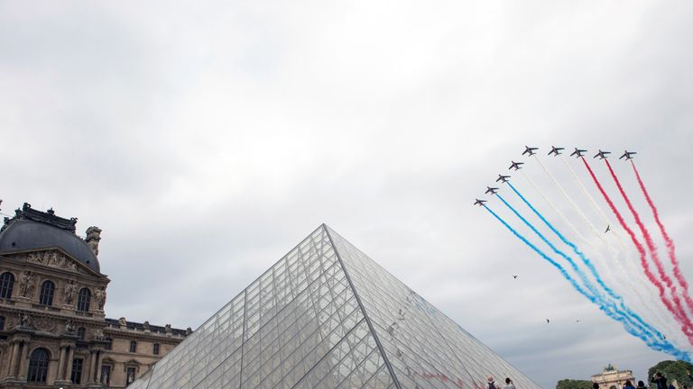 Jets fly in the sky over the Louvre museum in Paris