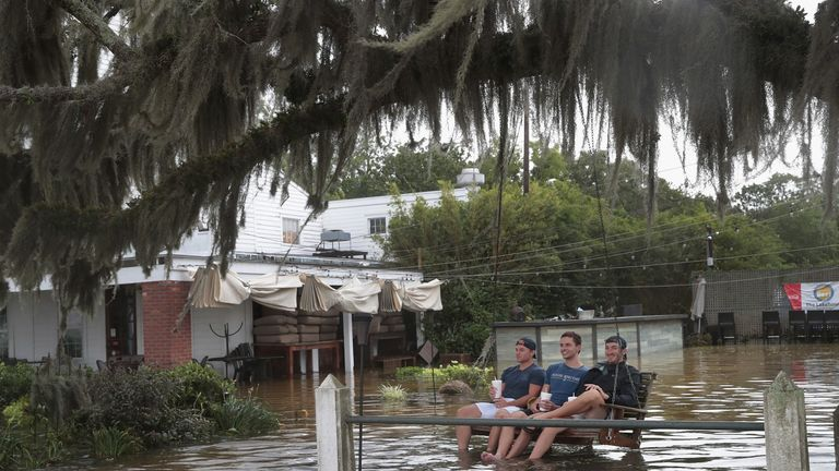 People sit in a swing surrounded by water from Lake Pontchartrain after the area flooded in the wake of Hurricane Barry on July 13, 2019 in Mandeville, Louisiana
