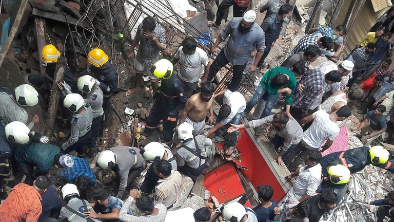 Rescue workers and residents search for survivors at the site of a collapsed building in Mumbai, India