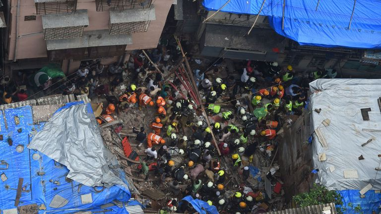 Indian fire brigade personnel and rescue workers look for survivors after a building collapsed in Mumbai