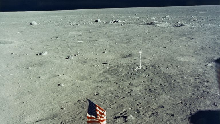 The United States flag is planted on the surface of the Moon by the astronauts of NASA's Apollo 11 lunar landing mission, as seen from inside the Lunar Module the 'Eagle', 20th July 1969. In the background is the black and white lunar surface television camera which televised astronauts Neil Armstrong and Edwin 'Buzz' Aldrin Jr during their EVA (extravehicular activity). (Photo by Space Frontiers/Getty Images)