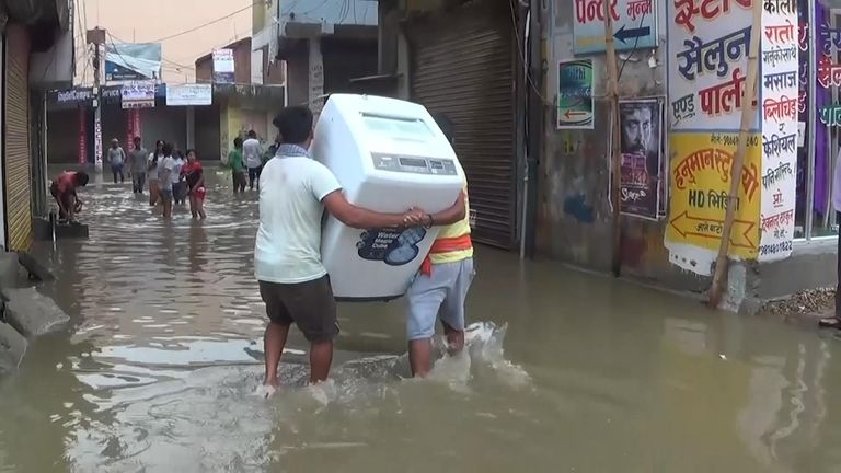 Men carry a fridge away from rising flood waters