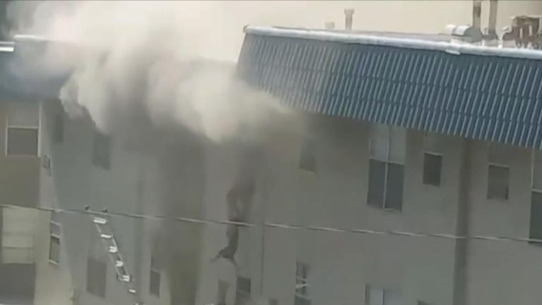 Workers rescue a family from a burning apartment.