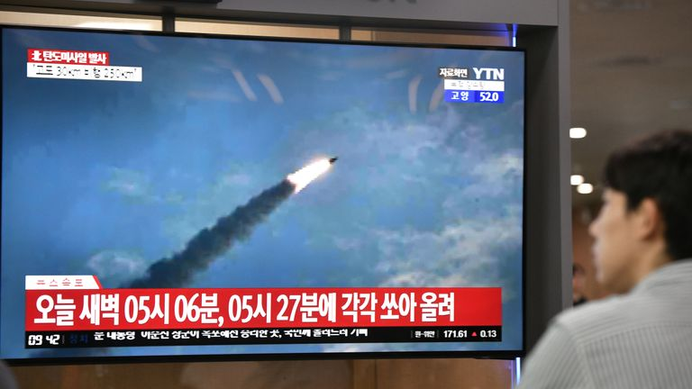 A man watches file footage of a previous North Korean missile launch
