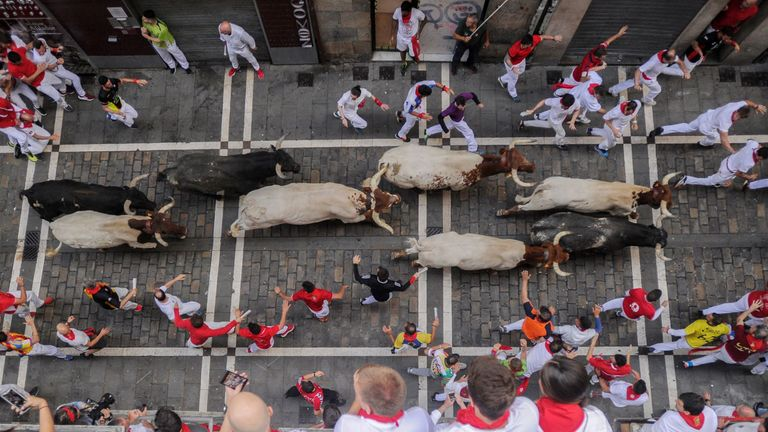 Revellers observe as participants run with Miura fighting bulls on the last bullrun of the San Fermin festival in Pamplona, northern Spain, on July 12, 2019. - People from around the world flock to the city of 200,000 residents to test their bravery and enjoy the festival's mix of round-the-clock parties, religious processions and concerts. (Photo by ANDER GILLENEA / AFP) (Photo credit should read ANDER GILLENEA/AFP/Getty Images)