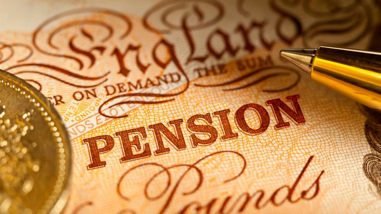 Sterling Pension Savings in the UK.  A Ten Pound sterling bank note with a pound coin and a ballpoint pen, with focus on the word Pension. From April 2015 aside from the 25% you are currently entitled to take as a tax-free lump sum from age 55 years,