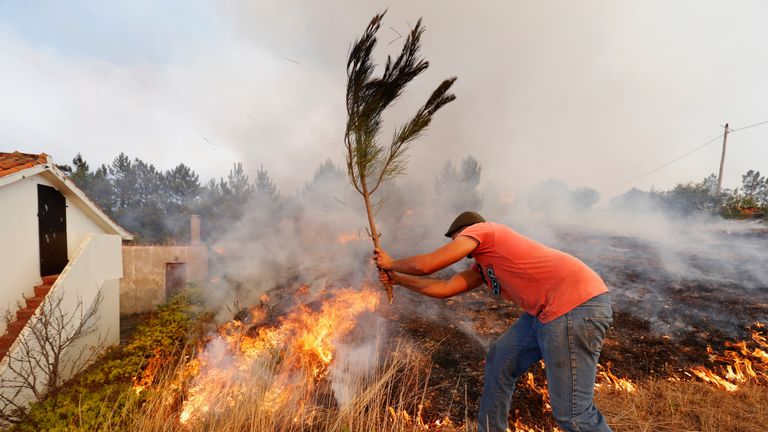 Villagers help to put out a forest fire at the small village of Colos, Portugal