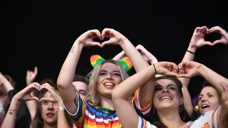 Fans hold their hands up in the shape of hearts during the Pride Cymru Big Weekend on August 25, 2018 in Cardiff, Wales