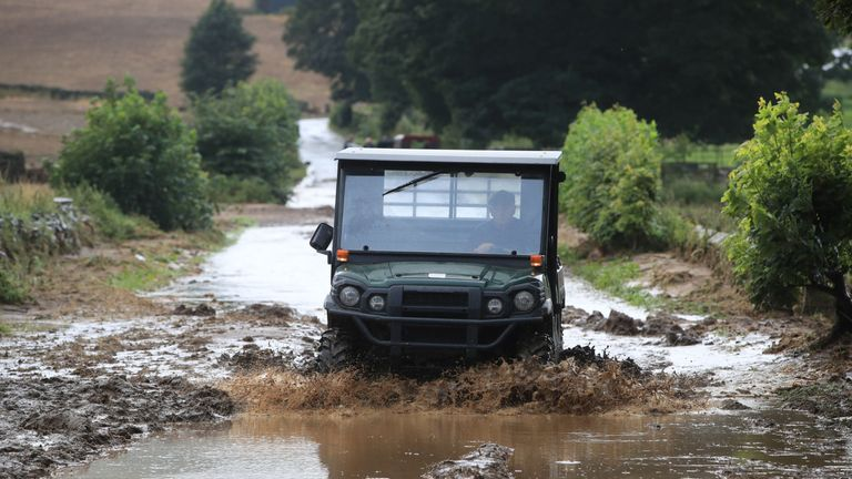 A man drives along a flooded road in Grinton, North Yorkshire