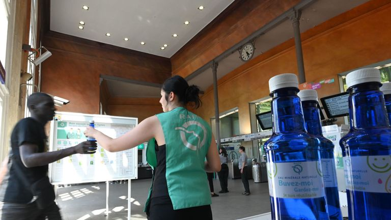 An agent of the RATP (Autonomous Operator of Parisian Transports) distributes bottles of water to commuters in Paris on July 23, 2019