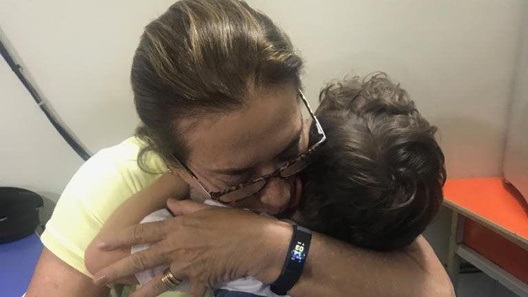 A teacher cuddles a pupil at Uere school in Rio de Janeiro
