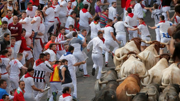 Runners let the bulls pass them on the final day of the San Fermin festival