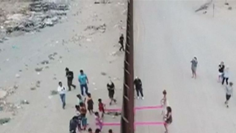 Fluorescent pink seesaws are an attraction on the US - Mexico border